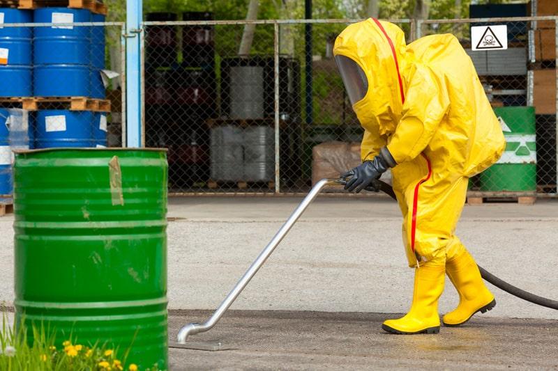 Worker in yellow hazmat suit cleaning ground
